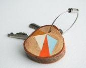 Pine wood keychain with stainless steel cable wire, pastel orange, orange, baby blue, and dark yellow geometric triangle shapes