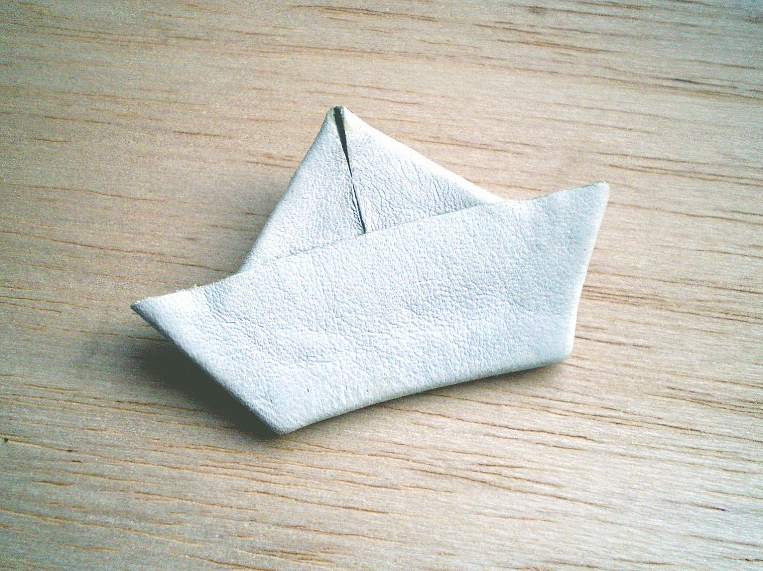 White paper boat pin, made of leather.