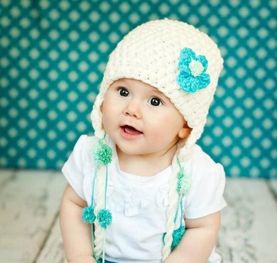 قلاب دوزی POM POM یکنوع عرقچین کوچک کهمحصلین برسر میگذارند کلاه با گل، سرپا نگه داشتن عکس برای نوزادان و کودکان