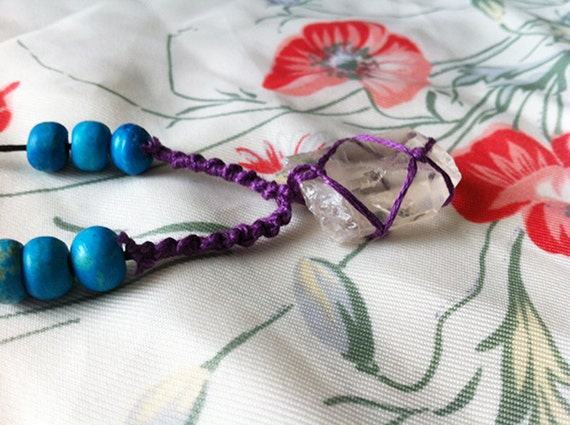 kai. netted quartz crystal necklace with wooden turquoise beads and purple thread.