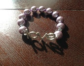Rhinestone 'Love' bracelet with pearlized mauve beads.  Mauve and purple. Fits most wrists.