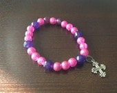 Silver tone cross charm bracelet. Pink iridescent beads. Purple and pink.  Fits most wrists.