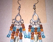 A teardrop chandler with a mix of brown and blue seed beads accented with a gold tone leaf.