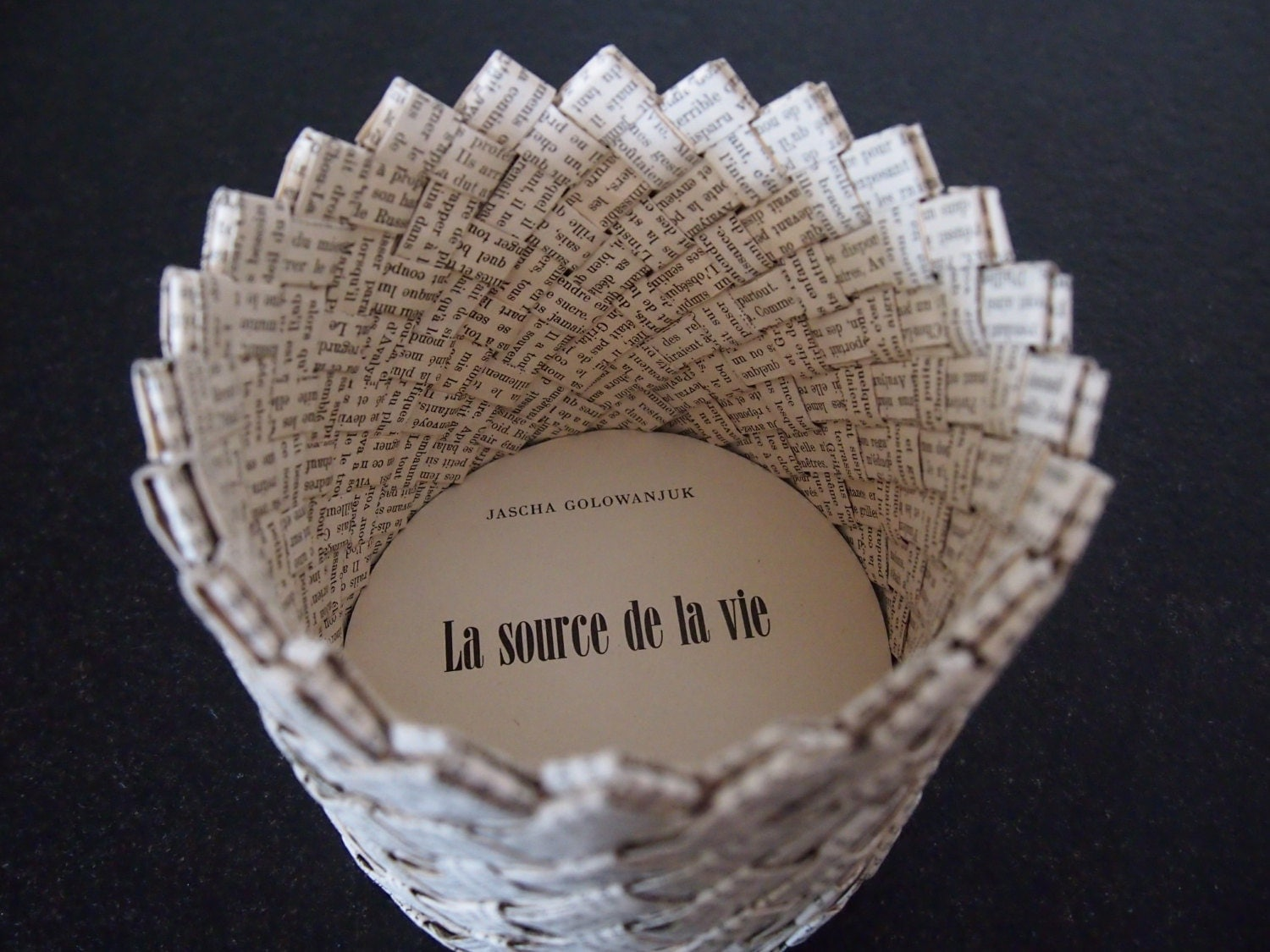 Paper storage basket woven from vintage book
