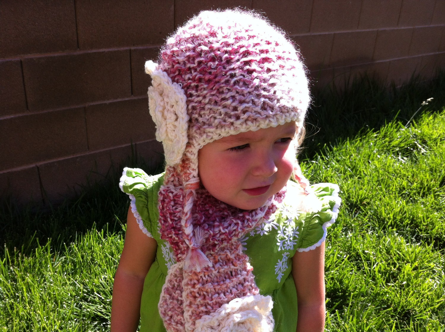 Children's Hand knitted hat, tassels and ear flaps with a large crochet flower - Color shown is Parfait