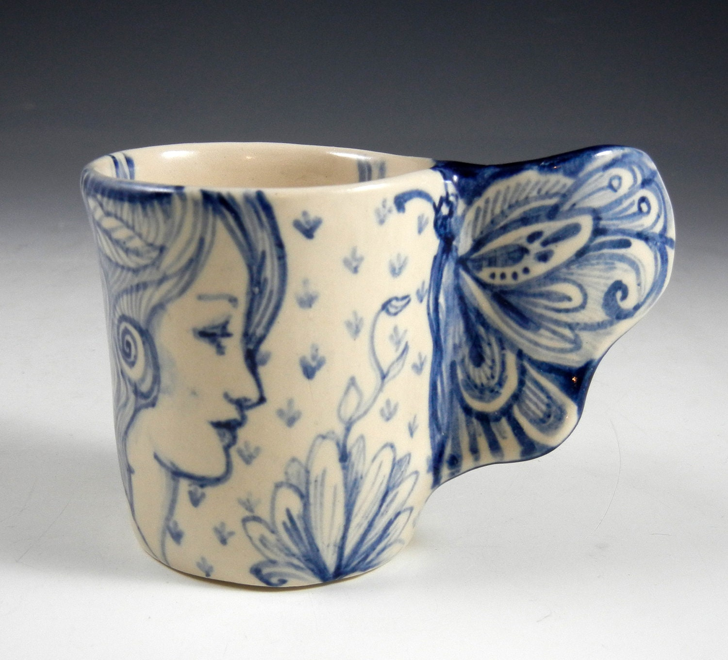 Blue and white porcelain cup with butterfly wing and three faces