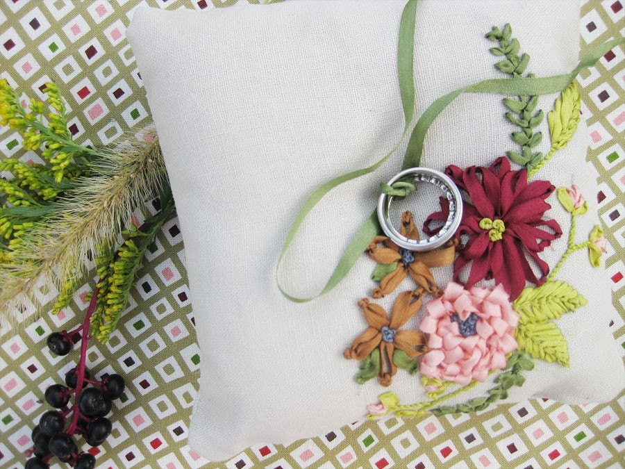 Ring pillow with ribbon embroidered flowers in coral and burgundy.