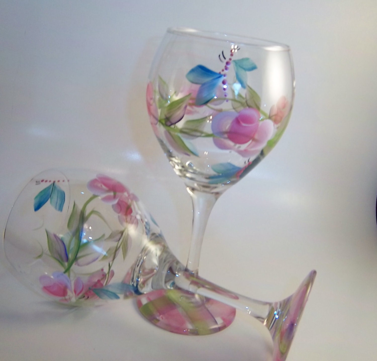 Hand painted wine glasses features rosebuds and butterflies.