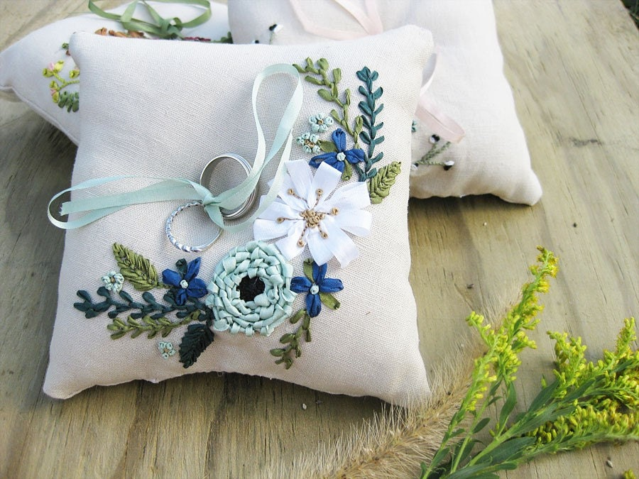 Ring pillow with ribbon embroidered flowers in deep blue, aqua, and white.