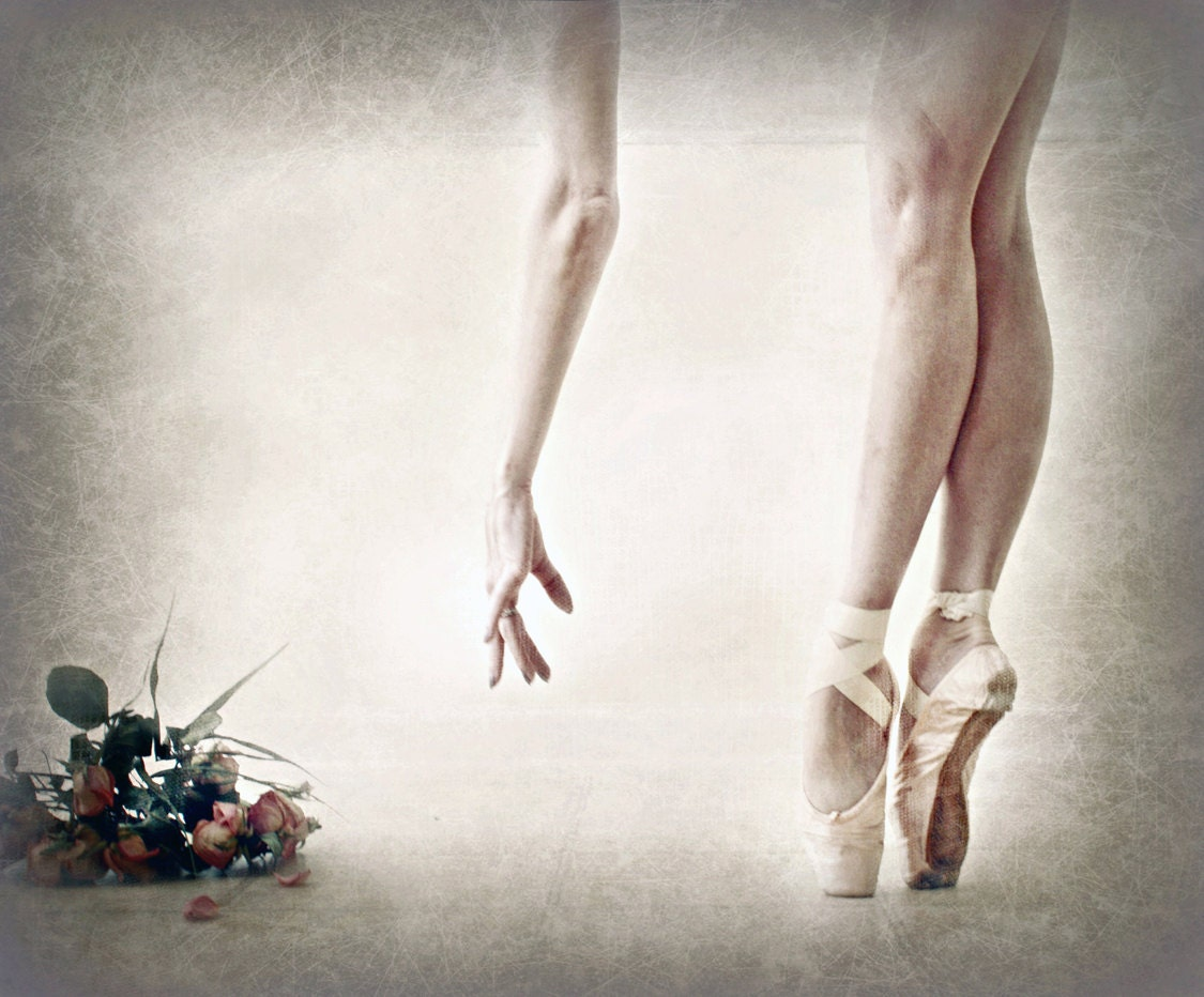 En Pointe.  Image of a dancer's legs and her hand reaching for a bouquet of roses at her feet.