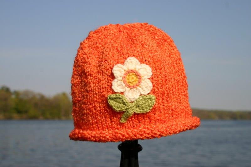 کودک کلاه بافتنی -- کلاه نارنجی دست بچه گره را با گل
