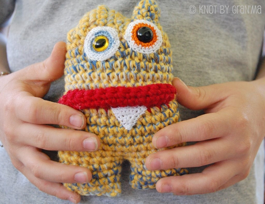 kiddo holding the mini monster ooak plush amigurumi in yellow