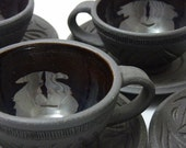 Four Carved Black Clay Tea cups and Saucers