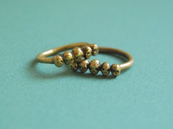 Golden row of tiny skulls ring