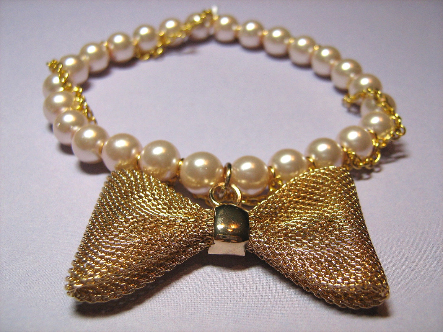 Stretch Bracelet: Pink Glass Pearls Wrapped with a Goldtone Metal Chain and Featuring a Goldtone Mesh Bow Metal Charm, for Women
